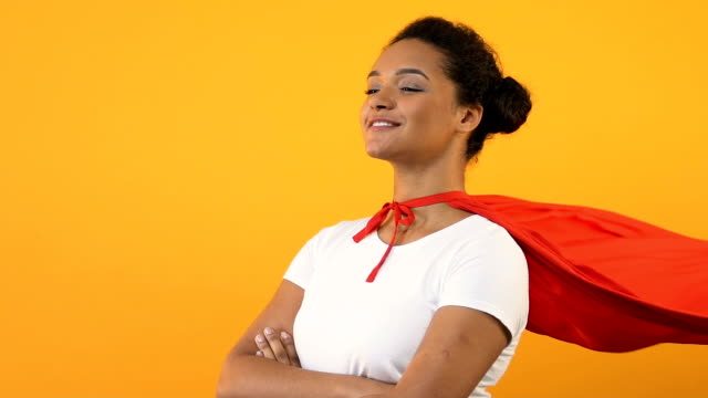 selbstbewusste afroamerikanischen frau mit gekreuzten händen im roten umhang, superhelden - held stock-videos und b-roll-filmmaterial