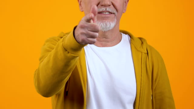 Self-confident aged male showing call me gesture, flirting date, communication