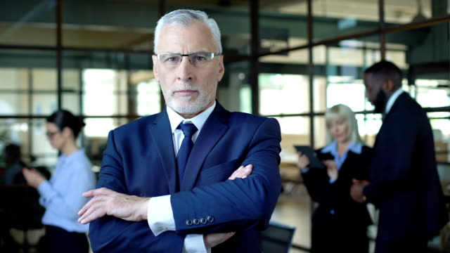 Self-confident aged man in suit looking camera, business leader, company career