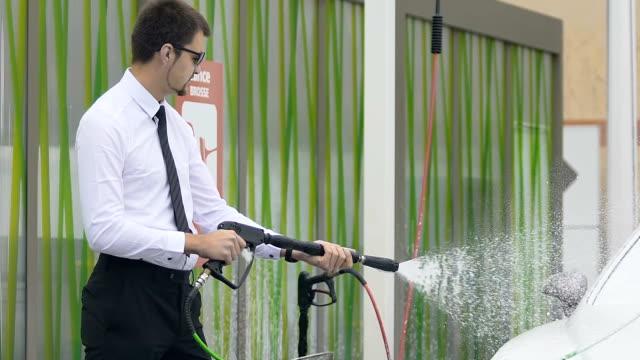 självsäker man tvätta dyra auto med vatten, ta hand om elit bil - surf garage bildbanksvideor och videomaterial från bakom kulisserna