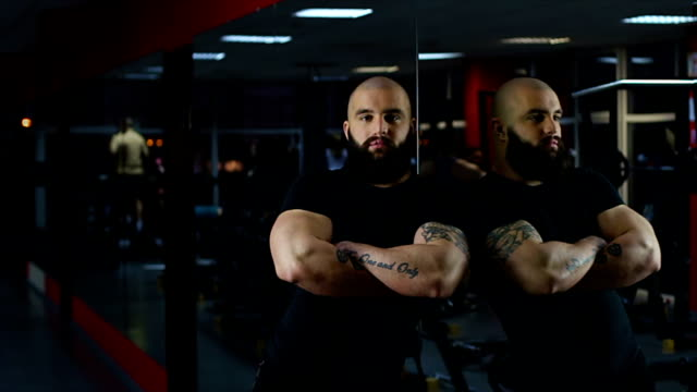 Self-confident muscular man looking at camera, people working out in gym, mirror video