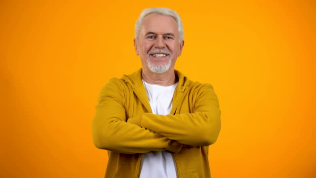 Self-confident senior man with folded arms smiling into camera healthy pensioner
