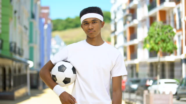 Self-confident teenage football player with ball looking on camera, challenge
