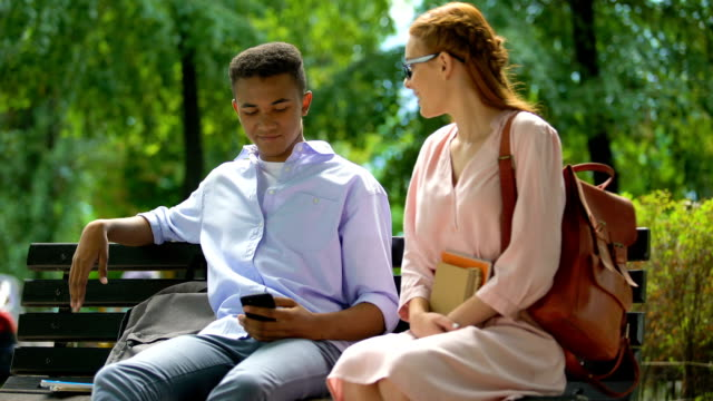 Self-confident teenager rejecting red-haired girl, first love relationship