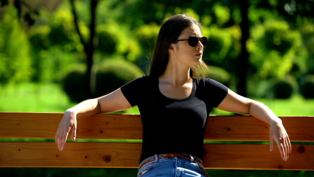 Self-confident woman in dark sunglasses sitting on bench in park looking around