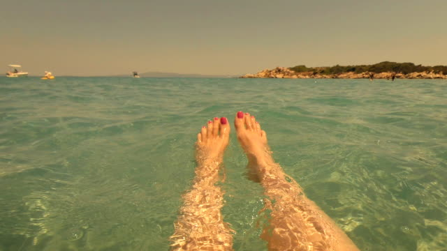 Selfie Beach Feet. Woman relaxing floating in the water. video
