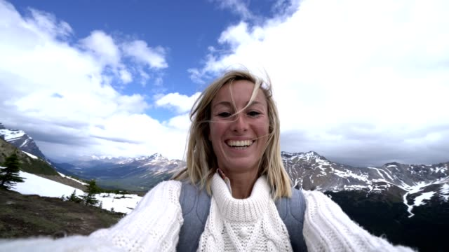 Selfie of young woman hiking on snowy trail above lake video