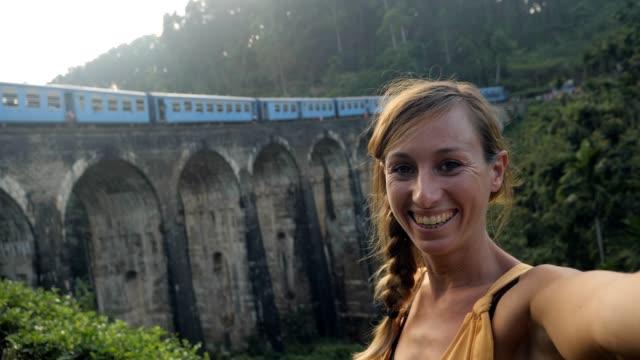 stockvideo's en b-roll-footage met selfie van jonge vrouw die in sri lanka reist en videovraag neemt terwijl de trein die op achtergrond overgaat. - camelia white