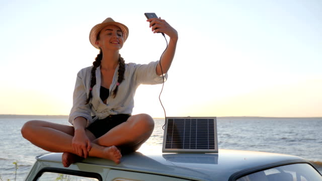selfie on vehicle in sunlight, girl sits on roof retro car in backlight makes photo selfie on phone video