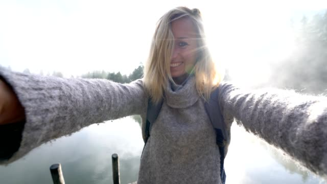 Selfie portait of young woman on lake pier in the morning fog, Switzerland video