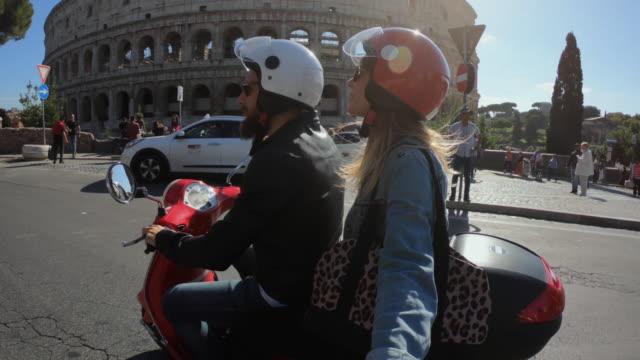 Selfie scooter riding: tourist couple on the motorbike by the Coliseum