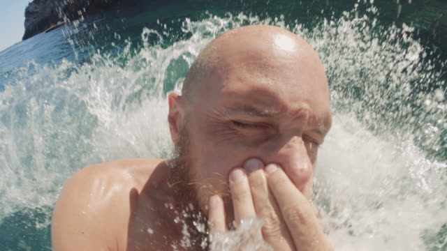 Selfie video of a man jumping and diving in a summer sea from a boat