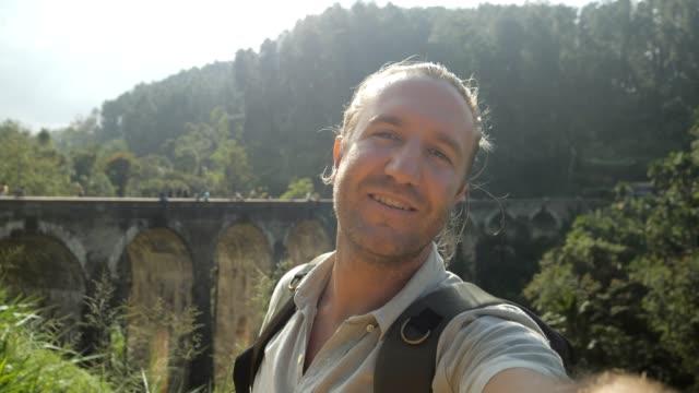 stockvideo's en b-roll-footage met de video van de selfie van gelukkige reismens in sri lanka dat mooie plaats met oude brug van de treinboog en de heuvels van de theeplantage toont. man video chatten online communiceren met mensen delen avonturen - camelia white