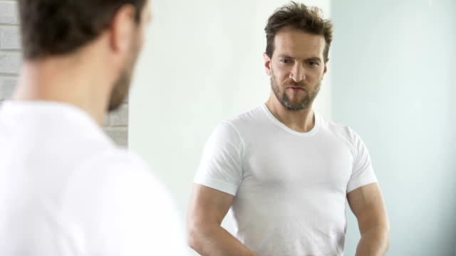 Selfish macho admiring and flirting with his reflection, self-improvement video