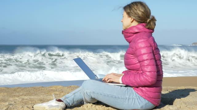 self-isolation from coronavirus, quarantine. woman freelancer with laptop work on beach - vídeo