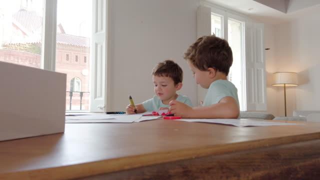 kendi kendine çalışma faaliyetleri. küçük çocuklar ev ödevi yapıyor. coronavirus salgını karantina - çalışma kitabı stok videoları ve detay görüntü çekimi