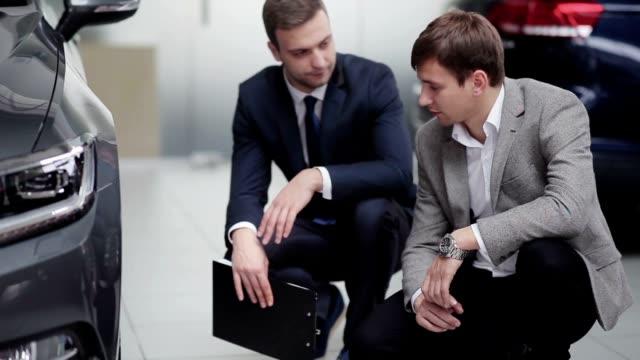 Seller and buyer having conversation near wheel