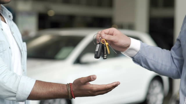 Seller gives a keys to a buyer in car showroom Close-up. The seller gives the automobile's keys to the customer. The buyer take a keys in hand. The man just bought a car into car showroom. The man buying the automobile in car dealership and takes a keys. car rental stock videos & royalty-free footage