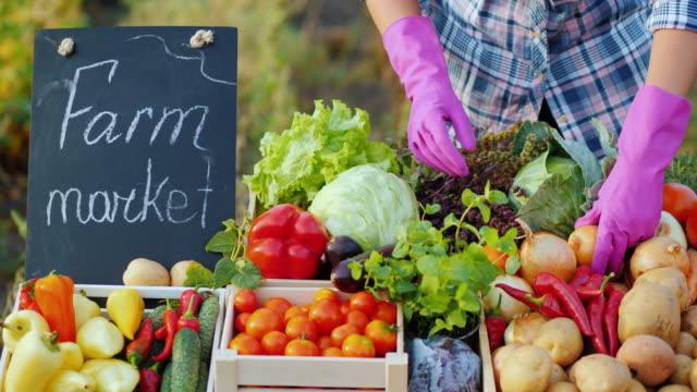 분홍색 장갑을 낀 판매자가 채소를 전시합니다. - 유기농 스톡 비디오 및 b-롤 화면