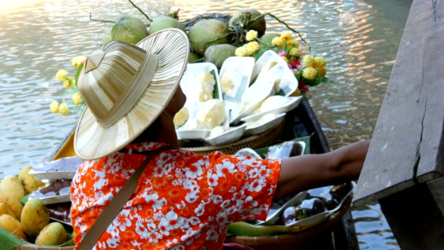 seller of exotic fruits on a boat and a straw hat sails on the river in thailand, on a floating market, pattaya - pattaya filmów i materiałów b-roll