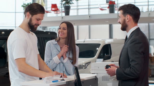 Seller signing contract, giving pen to man. Young guy putting signature on document. Seller giving keys of car on background of beautiful new cars. Seller signing contract, giving pen to man. Young guy putting signature on document. Seller giving keys of car on background of beautiful new cars car shopping stock videos & royalty-free footage
