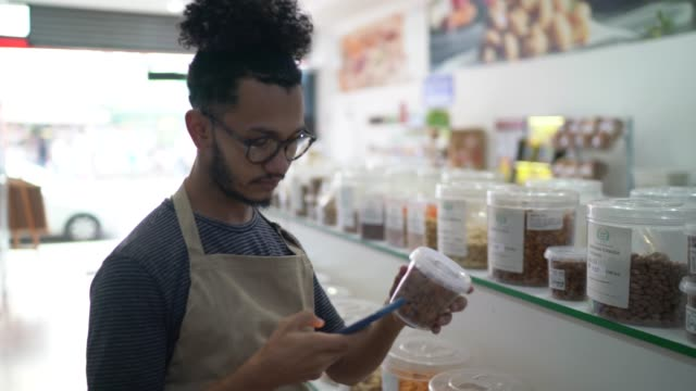 Seller using smartphone to check products in a natural products store Seller using smartphone to check products in a natural products store market retail space stock videos & royalty-free footage