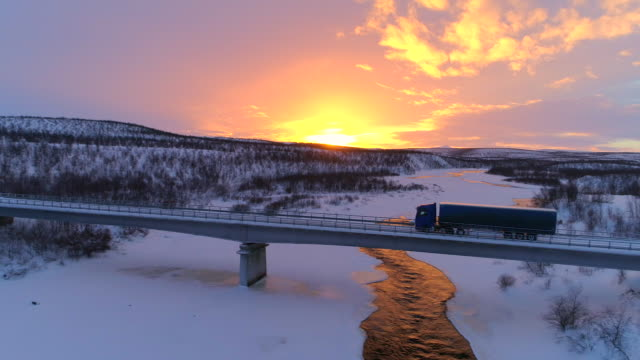 AERIAL: Semi truck crossing the bridge above icy river in the winter at sunset