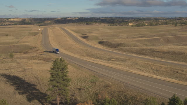 AERIAL: Semi truck hauling goods along busy rural hilly landscape highway video