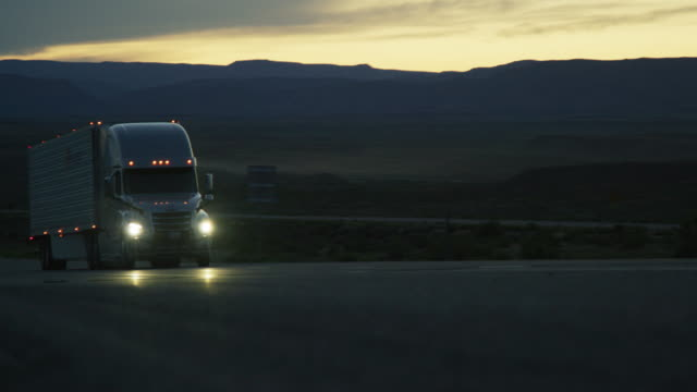 a semi truck with headlights on drives in the high desert of western colorado at dusk - тягач с полуприцепом стоковые видео и кадры b-roll