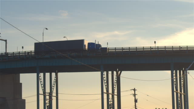 LOW ANGLE VIEW: Semi trucks driving on the overpass transporting goods at sunset