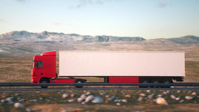 vidéos et rushes de camion semi-remorque conduisant le long d'une route déserte - vue latérale