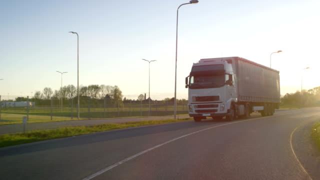 半トラック貨物トレーラーが高速道路で移動します。白いトラック輸送貨物産業倉庫のエリアを通過。 - トラック点の映像素材/bロール