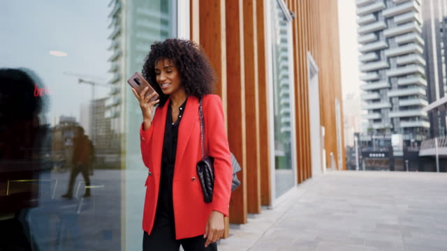 Sending voice messages on the move Beautiful businesswoman in read coat on her way to work place fashionable stock videos & royalty-free footage