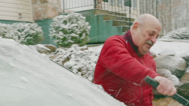 Senior 69-years-old man cleaning car from snow in the winter.