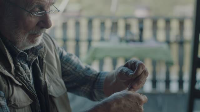 senior aktiver mann vorbereitung des köders - angelhaken stock-videos und b-roll-filmmaterial