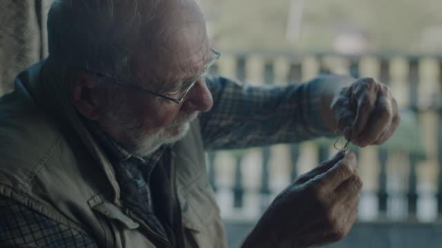 senior aktiver mann vorbereitung des köders - fischköder stock-videos und b-roll-filmmaterial