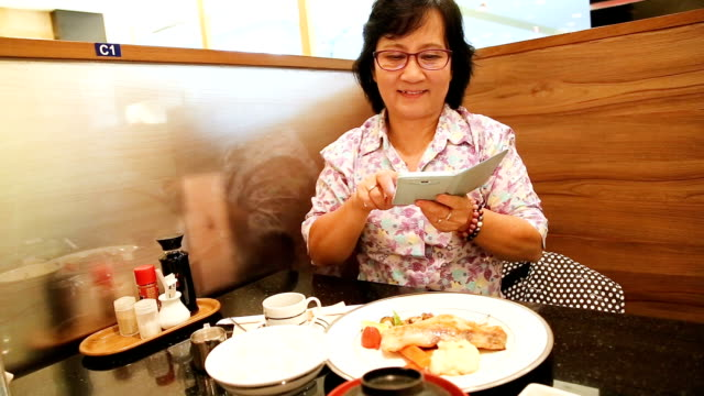 Senior adult Asian woman taking pictures of japanesef ood by smartphone. Full HD MS Senior adult Asian woman taking pictures of japanesef ood by smartphone. fat nutrient stock videos & royalty-free footage