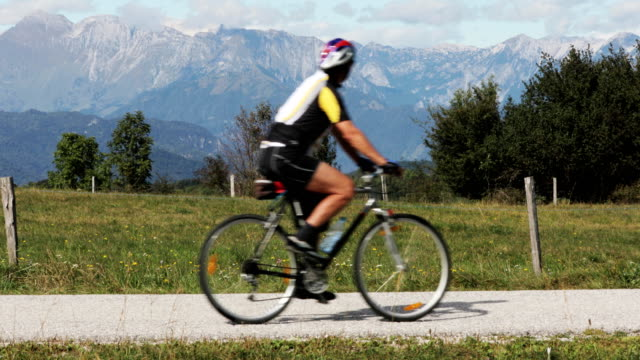 senior adult cycler moving past on country road - vorbeigehen stock-videos und b-roll-filmmaterial