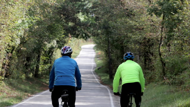senior adult cycling friends on the move on country road - fianco a fianco video stock e b–roll