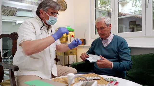 病気の患者から口のサンプルを取る上級成人医師 ビデオ