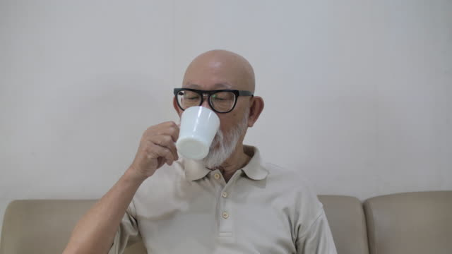 Senior adult drinking coffee at home