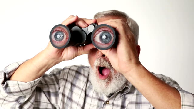 Senior Adult Man Looking Through Binoculars with Magnified Eyeballs video
