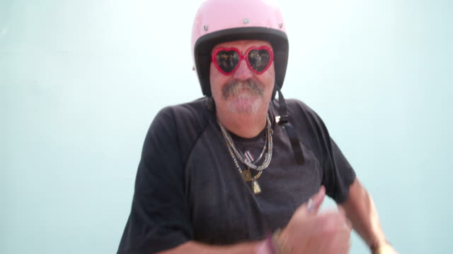 senior adult man wearing pink helmet and dancing - baffo peluria del viso video stock e b–roll