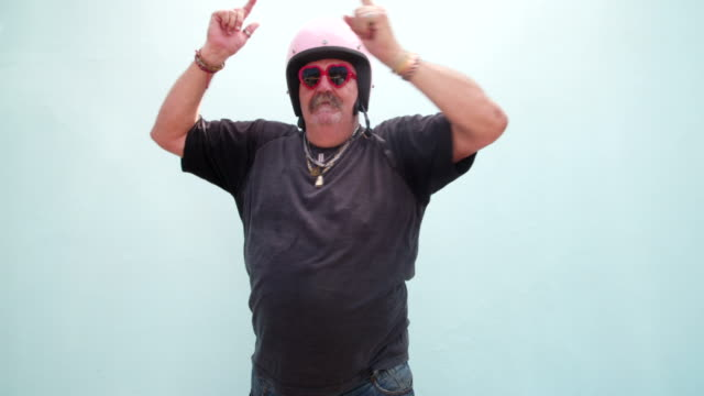 Senior adult man wearing pink helmet and dancing Silly senior adult man with pink safety helmet and red heart shape sunglasses dancing , isolated on blue wall background work helmet stock videos & royalty-free footage