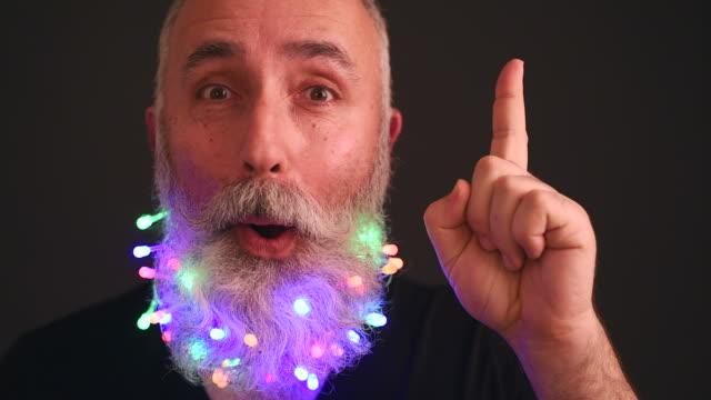 üst düzey yetişkin adam sakallı noel çelenk ile dekore edilmiş bir fikirdir - eksantrik stok videoları ve detay görüntü çekimi