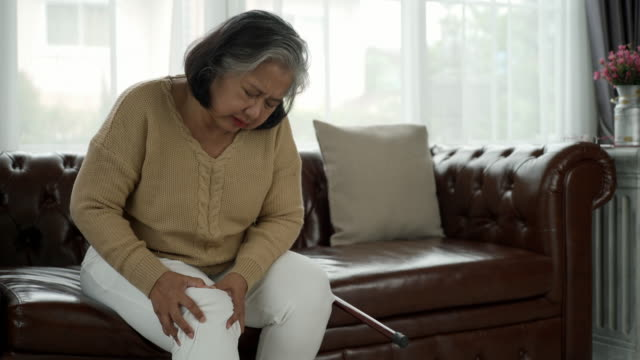 Senior Adult With Serious Legs and knee Pain Senior adult with a painful expression from a serious legs and knee pain having difficulty getting up, sitting down on the sofa and moving around the house thai ethnicity stock videos & royalty-free footage