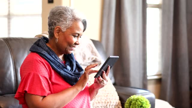 Senior adult woman at home using digital tablet. video