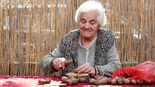 senior adult woman cracking walnut with hammer video