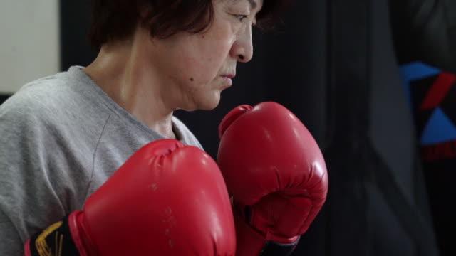 vidéos et rushes de sacs de sable frapper une femme adulte senior - seulement des japonais