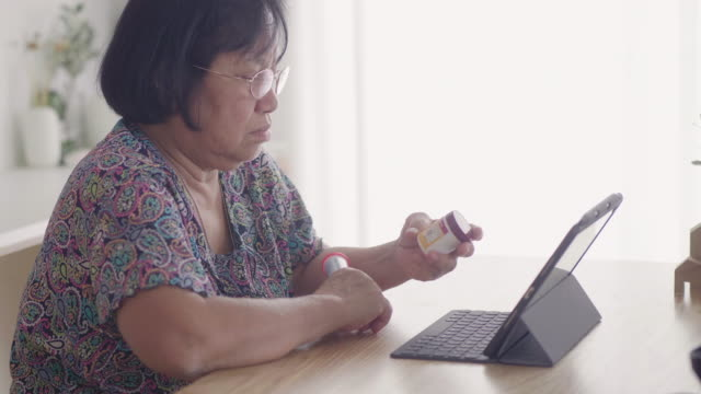 Senior Adult woman reading about medicine at home Asian senior woman with digital tablet checking prescription label in living room at home. pill bottle stock videos & royalty-free footage